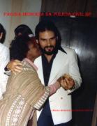 """Investigador de Polícia José de Freitas Mendonça """"in memorian"""" (posteriormente Delegado) e a lendária proprietária do barzinho improvisado do 3º andar do DEIC, Dijanira """"Dija"""", na década de 70. De costa, ao fundo o Delegado Carlos Harich."""