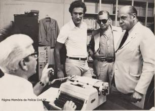 Investigador de Polícia Antônio Thomaz na máquina de escrever, na antiga Delegacia de Estrangeiros do DOPS, em 1.977. De pé, o jogador uruguaio Pedro Virgílio Rocha, que jogou na década de 70 no São Paulo Futebol Clube, regularizando sua documentação. Ao lado dele, dois diretores do SPFC, sendo um deles o advogado Vianna de Moraes.