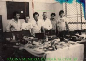 """Apreensões de Metralhadoras de assaltantes de Banco, em 1984: Da esquerda para a direita: 1- Investigador Chefe da Delegacia de Roubo a Bancos Oscar Matsuo, 2- Flaviano Mandruca (unico Escrivão de trabalhava como Investigador), 3- Investigador Luis Carlos dos Santos """"China"""" (Ex- DGP Adjunto), 4- Valsimir Cesar Constantino da Silva """"Canalha, in memorian"""", 5- Antonio Carlos Galdino e 6- Ricardo Romero """"Zé Galinha""""."""