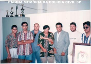 o centro, o Reporter Policial Gil Gomes, com a Equipe F Sul da Divisão de Homicídios. A partir da esquerda, o Escrivão Antonino Vasconcellos, hoje advogado; Agente Policial Dário; Iinvestigadores Hélder, Osvaldo Jose Dos Santos; Escrivão Fausto Bernardini e Investigador Alexandre.