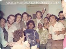 """Delegacia de Roubos do DEIC, década de 70: Da esquerda para a direita, Investigadores Luis Cesar Regina """"Batata, in memorian""""; (?); Paulinho; (?), Alfredo """"Farofa"""", Eládio """"Cavalo de Aço"""", Orestes, Paraguaio e Amadeu. À frente """"Nega Dija"""" e a Investigadora Jandira Maranhão """"Janda, in memorian""""."""