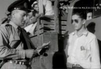 """Policial da extinta Guarda Civil do Estado de São Paulo fiscalizando um caminhão """"pau-de-arara"""", utilizado para o transporte de migrantes da região nordeste do País, na década de 40."""