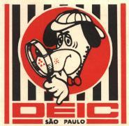 """Emblema do DEIC. Foi idealizado pelo Investigador de Polícia Célio Mello e elaborado pela Horse's Promoções Ltda, em março de 1.969. Suas características: Sobre um quadrado, treze barras verticais, para evocar as cores dominantes da Bandeira do estado de São Paulo; ao centro, num círculo, a figura do personagem de filmes de desenho animado do Hanna- Barbera, com uma lupa, personifica um astuto detetive em trabalho de investigação; embaixo onde iniciam as barras em preto e branco, a sigla """"DEIC"""" e, sob esta, o nome do Estado."""