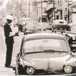 Um Guarda Civil do trânsito multando um veículo Gordini estacionado irregularmente, no início da década de 60.