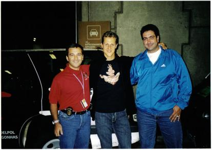 """Investigadores de Polícia Conrado Vivona Jr. e Augusto Resende, com o piloto de Fórmula 1 Michael Schumacher ao centro. Sem teto para o helicóptero do piloto levantar vôo, os policiais deram """"carona"""" para ele até o Aeroporto de Guarulhos."""