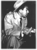 """Repórter Policial Maurício de Souza: Dick Tracy entrando na chefatura de polícia? Bem, o personagem usava capa de chuva e chapéu, como o detetive das tiras dos jornais americanos da década de 1930. Mas não era um detetive, era um repórter policial. Não estava nos States, mas na moderna São Paulo de 1957. A chefatura era na verdade a Central de Polícia, ao lado do Pátio do Colégio. A vestimenta do repórter ficava um tanto deslocada, mas ele não se importava. Seu nome: Maurício de Souza. Ficou um ano nessa vida. Depois seguiu seu destino de desenhista e inventou Bidu, Franjinha e toda a turma da Mônica. Ele dizia que se fantasiava de detetive americano porque era tímido. Vestido como herói, tinha coragem para falar."""" . Além da timidez, Maurício de Souza tinha aquele outro sério problema. """"Era uma coisa horrível, eu não podia ver sangue que desmaiava"""". No local de um crime, pedia socorro ao fotógrafo. """"Ele olhava o corpo e me dizia como estava, se era em decúbito ventral (barriga para baixo)"""" - conta, divertindo-se com o linguajar técnico. Cama de casal – Maurício trabalhava de madrugada. Naquelas em que nada acontecia, e como não aderisse ao jogo, juntava as mesas (podia ser a da Folha, onde trabalhava, a dos Diários, a da Última Hora, do Estadão), e assim tinha uma cama """"grande como de casal"""". Fazia um travesseiro de jornais amassados, deitava-se e dormia... É verdade que, em plena madrugada, podia ser incomodado por uma notícia. Neste caso, pedia condução e fotógrafo, e a Folha da Manhã (hoje Folha de S. Paulo) mandava o carro da reportagem, um jipe laranja. Podia chegar também o jipe dos Diários Associados (que Bussab, em outras horas, também usava). Naquela época, a periferia da cidade não era asfaltada. Muitas vezes Maurício se deparava com um crime passional, o marido pegou a mulher com o amante, ou vice-versa. """"Na confusão, a família chorando, eu cumpria ordens do jornal: roubava a foto do casamento."""" Era ótima ilustração para a reportagem. Maurício achava """"uma"""