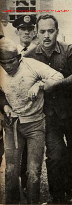 "O Investigador Luiz Gonzaga Garcez da Delegacia de Roubos do DEIC, o ""Kilo"", conduzindo preso o famigerado marginal João Alves da Silva ""Boca de Traíra"", em 12 de fevereiro de 1970. https://www.facebook.com/MemoriaDaPoliciaCivilDoEstadoDeSaoPaulo/photos/a.372880226167888.1073741849.282332015222710/1094240077365229/?type=3&theater"