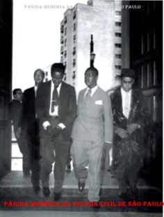 """Prisão do ladrão do carro forte no bairro do Cambuci, Guaraci Ramos Teixeira """"Guaracizão"""" do Lavapés, em 05.02.1957, realizada por policiais da Delegacia de Vigilância e Capturas do Departamento de Investigações, que integravam uma equipe da RUDI. As fotos representam um marco histórico para quem conheceu o antigo Departamento de Investigações, o famoso """"D.I."""", cuja sede ficava na Rua Brigadeiro Tobias, nº 527, bairro da Luz. 1) Ao velho estilo americano, sob o olhar do investigador Washington Gomes de Campos """"Campinho"""", ao lado o Delegado Glauco de Devitis e o Investigador Bruno, sendo o detido algemado e de cabeça baixa. 2) Entrada principal do Departamento de Investigações (observando-se ao fundo, que naquele tempo, não existia o prédio do Ministério da Fazenda na Avenida Prestes Maia). ( Acervo do filho, o Advogado Dermeval Gomes de Campos)."""