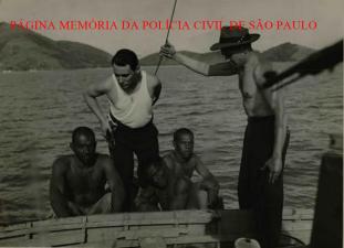 """Nesta embarcação frágil, 3 presos que participaram da grande rebelião do Presídio da Ilha Anchieta, em 1.952, foram recapturados pelos enviados do Jornal """"Última Hora"""" para cobrirem o fato, destacando-se a corágem do Reporter Policial Nelson Gatto, ao centro."""