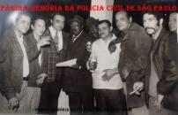 """Equipe Norte da DISCCPAT (Kilo), do DEIC, em uma das tradicionais reuniões no Clube Estrela do Pari, em 1.974. À partir da esquerda, Investigadores Landinho (trabalhou posteriormente no arquivo de fichas criminais com o Chefe Ivan), Momoki Akimoto; Delegado Getúlio Paello Prado; o humorista Dorival Silva """"Chocolate""""; Agente Policial Nughet; Investigadores Severino, Luiz Melli """"Luizão"""" (parceiro de trabalho do Paulo Artusi """"Pinduca""""); Milton Baco e (?). (Acervo do filho do Dr. Getúlio, Investigador Alberto Prado)."""