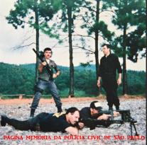 Policiais do GARRA, no Curso da SWAT, realizado no stand de tiro da Rodovia Castelo Branco, em 1.995. De pé, trajando macacão preto, o Delegado Pedro Carabina e deitado sem boné, o Investigador Marco Quaranta.