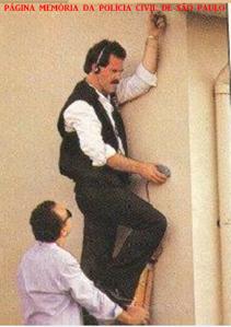 Delegado de Polícia da 5ª Delegacia de Roubo a Bancos da DISCCPAT- DEIC (Kilo), Elson Alexandre Sayão, efetuando escuta através de parede, na década de 80.