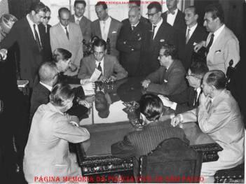 """AFPESP- Associação dos Funcionários da Policia Civil do Estado de São Paulo, em 15/07/1958. O presidente que esta na cabeceira à esquerda da mesa Investigador Mario Gonçalves, segurando e lendo uma pauta e em pé às suas costas de terno escuro seu irmão Décio, também investigador; . À partir da esquerda, o quarto é o Investigador de policia Miguel Franco. o 6º o Investigador Francisco Alpiste Gomes, foi Oficial de Gabinete do Secretário da Segurança Ataliba Leonel, no Governo de Jânio da Silva Quadros em 1958. De óculos, de pé, Escrivão Alcides Rocha. Atrás da foto os dizeres: """"Ao meu amigo e colega Miguel Franco ofereço como lembrança das nossas lutas em favor das classes policiais"""". Mario Gonçalves - Presidente - 15/07/1958."""