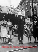 Integrante da extinta Guarda Civil do Estado de São Paulo, auxiliando crianças e mulheres atravessarem a avenida, em frente ao antigo Mappin. na década de 60. https://www.facebook.com/MemoriaDaPoliciaCivilDoEstadoDeSaoPaulo/photos/a.359815487474362.1073741848.282332015222710/1086969154758988/?type=3&theater