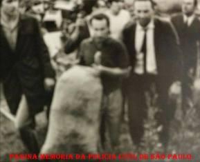 """Prisão de um dos maiores traficantes da Zona Norte e Leste de São Paulo, na década de 60, José Bernardes da Silva """"Zezinho da Vila Maria"""", carregando um dos sacos de """"maconha"""" apreendido, ao lado o Guarda Civil optante Investigador José Alves da Silva """"Zé Guarda"""", ao fundo de camisa branca o Investigador Delauri, à direita Investigador Hélio Teixeira e de capa preta à esquerda, o Repórter Policial Afanásio Jazadji, em 02 de dezembro de 1.969."""