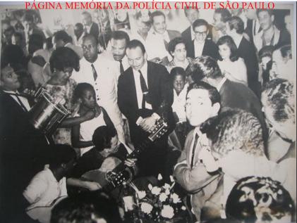 """Festa de Final do Ano 1963 para 1964, na mansão no Bairro do Pacaembú, do saudoso Delegado Chefe da RUDI, José Carlos Baptista """"Zebú"""" (oriundo de família abastada de comerciantes paulistanos), ao centro de terno preto. Na foto, o Investigador Chefe, Washington Gomes de Campos """"Campinho"""" e esposa Dona Tereza; Investigadores Walter Rodrigues """"Manteiga"""", Joaquim Olacyr (no fundo), Rinaldo Correia (irmão do Reinaldo Correa), Carlos Brandão Leite (Carlito Cara de Pau), Augusto Waldemar Veneziano e Jadala Risk, apreciando o som dos instrumentos tocados por Germano Matias, Jorge Ben e José Provetti """"Gato"""" (guitarrista solo do Conjunto Jet Black's e depois do RC 7 de Roberto Carlos). Esteve nesta festa, o Dr. Coriolano Nogueira Cobra e outros Cardeais da Polícia Civil. Acervo do Advogado Dermeval Gomes Campos """"Campinho""""."""