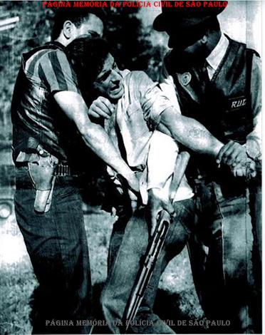 """Detenção de um """"caranguejeiro"""" (ladrão de carro), em 23 de julho de 1.964, pelos Investigadores Washington Gomes de Campos """"Campinho"""" e Ivan Garcia, da RUDI. Detalhes do célebre colete preto da RUDI e do magnificente distintivo do Corpo de Segurança de São Paulo na lapela. (Acervo do Advogado Dermeval Gomes de Campos)."""