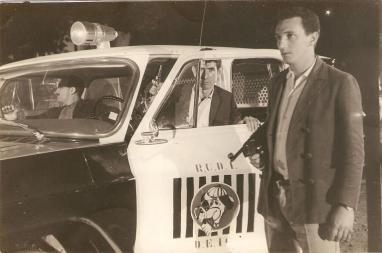 """RUDI (RONDAS UNIFICADAS DO DEPARTAMENTO DE INVESTIGAÇÕES). Investigador Iguatemi Campão no banco de passageiro e saindo da viatura o Sílvio """"Caroço"""" Mariano."""