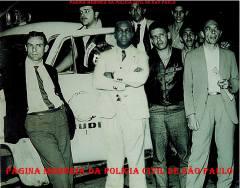 """Em frente a Casa do Delegado Chefe da RUDI José Carlos Baptista """"Zebú"""", no Bairro do Pacaembú, na festa da passagem dos anos 1.963/1.964). À partir da esquerda, o Motorista Policial """"Chapéu"""", Investigadores Osvaldo Peixoto da Silva, Washington Gomes de Campos """"Campinho"""", Sother Evaristo Wenceslau , Newton de Moraes Coelho e repórter (?). (Acervo do advogado Demerval Gomes)."""