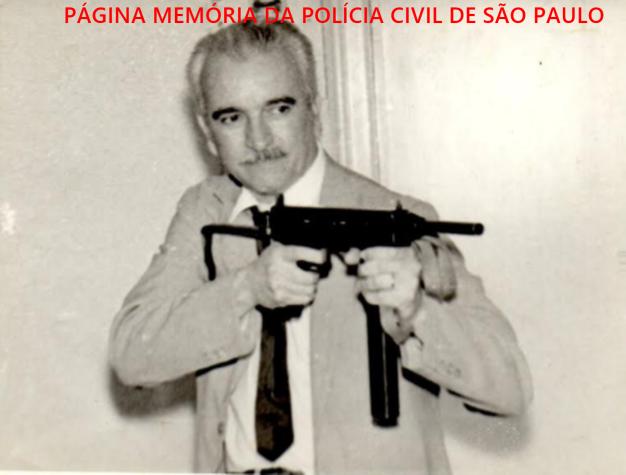 """Dependências da DISCCPAT do DI- Departamento de Investigações """"Kilo"""", em meados da década de 60. O Chefe dos Investigadores Synesio Chavasco Filho posando para foto armado com uma metralhadora. Acervo de Nico Chavasco. https://www.facebook.com/MemoriaDaPoliciaCivilDoEstadoDeSaoPaulo/photos/a.372880226167888.1073741849.282332015222710/1409863209136246/?type=3&theater"""